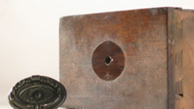 The finish on this 100-year-old drawer front is badly crazed everywhere except where the finish was shielded from light by the hardware.
