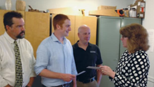 Evan Kistler (blue shirt) receives the award from DMT vice president Stacey Brandon.