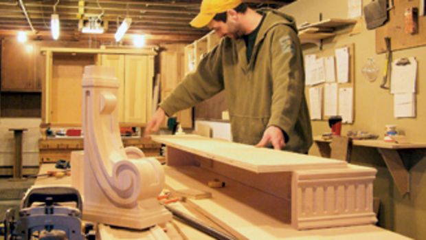 Russell Hudson Jr. assembles pieces for a fireplace mantle at his father's shop.