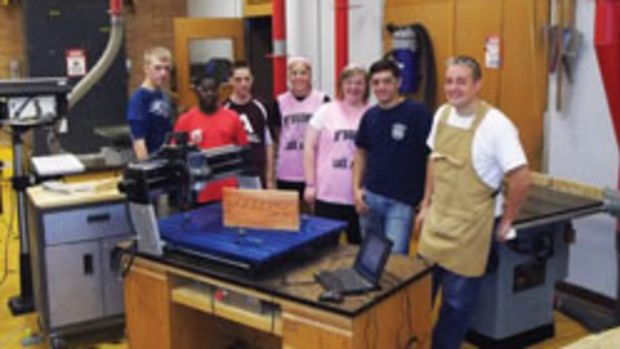 Justin Herrling shows his students how to work with the Rockler CNC machine he paid for with a local grant.