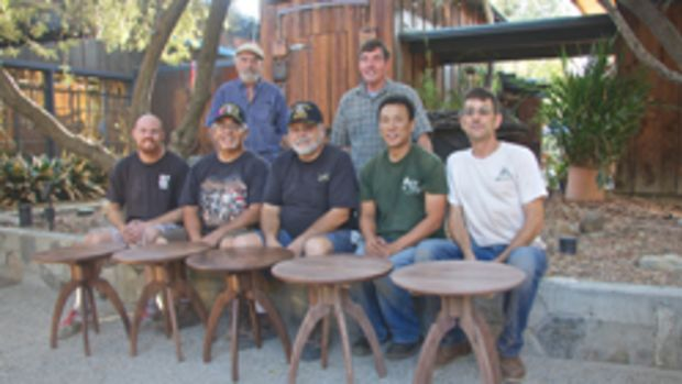 Veterans with their completed tables, made of walnut from Maloof's wood barn.