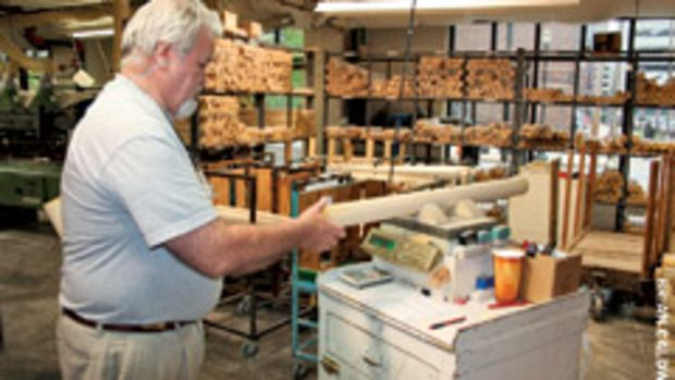 """Danny Luckett, CNC operator for the pro bat department at Hillerich & Bradsby Co., weighs a 3"""" x 37"""" ash billet to ensure it meets quality standards."""