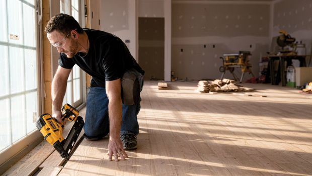 Photo of man using a power nailer to lay a floor