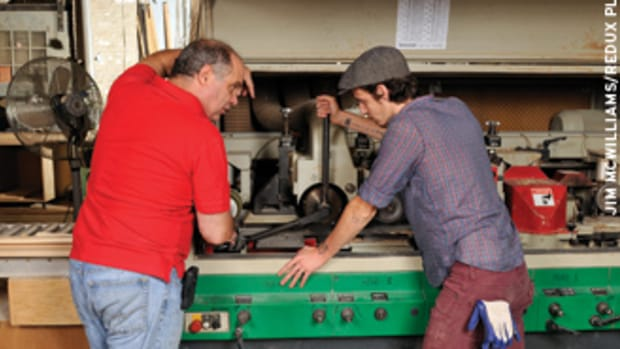 Co-owner Carmen Vona (left) goes under the hood of the shop's Weinig molder with employee Craig Cody.