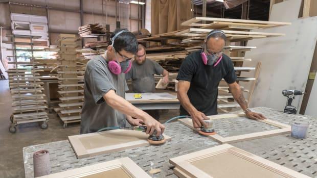 men-sanding-with-electric-sanders-masks