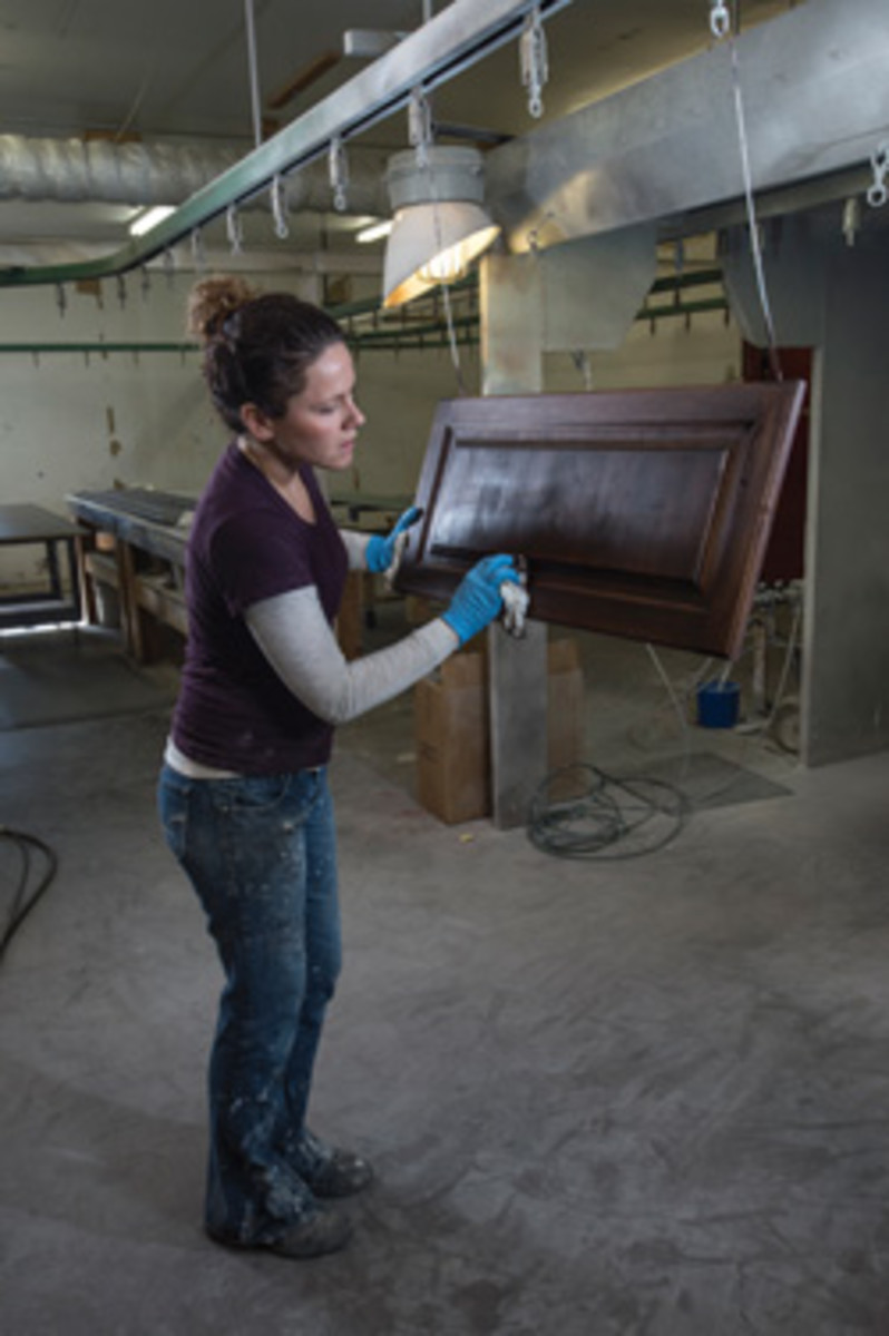 Carrie Bader, the shop's finishing manager, applies a final varnish.