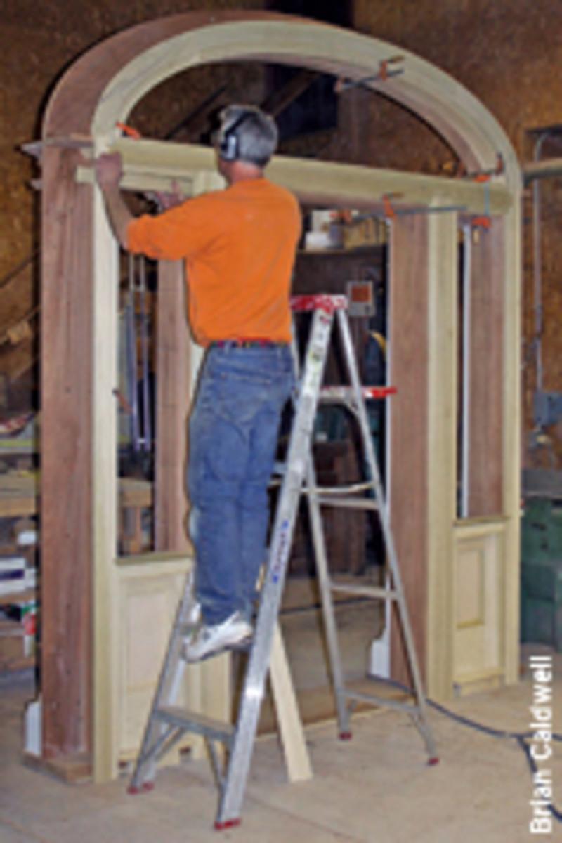 Shop foreman Brad Douglas works on the elliptical top of the front entrance.