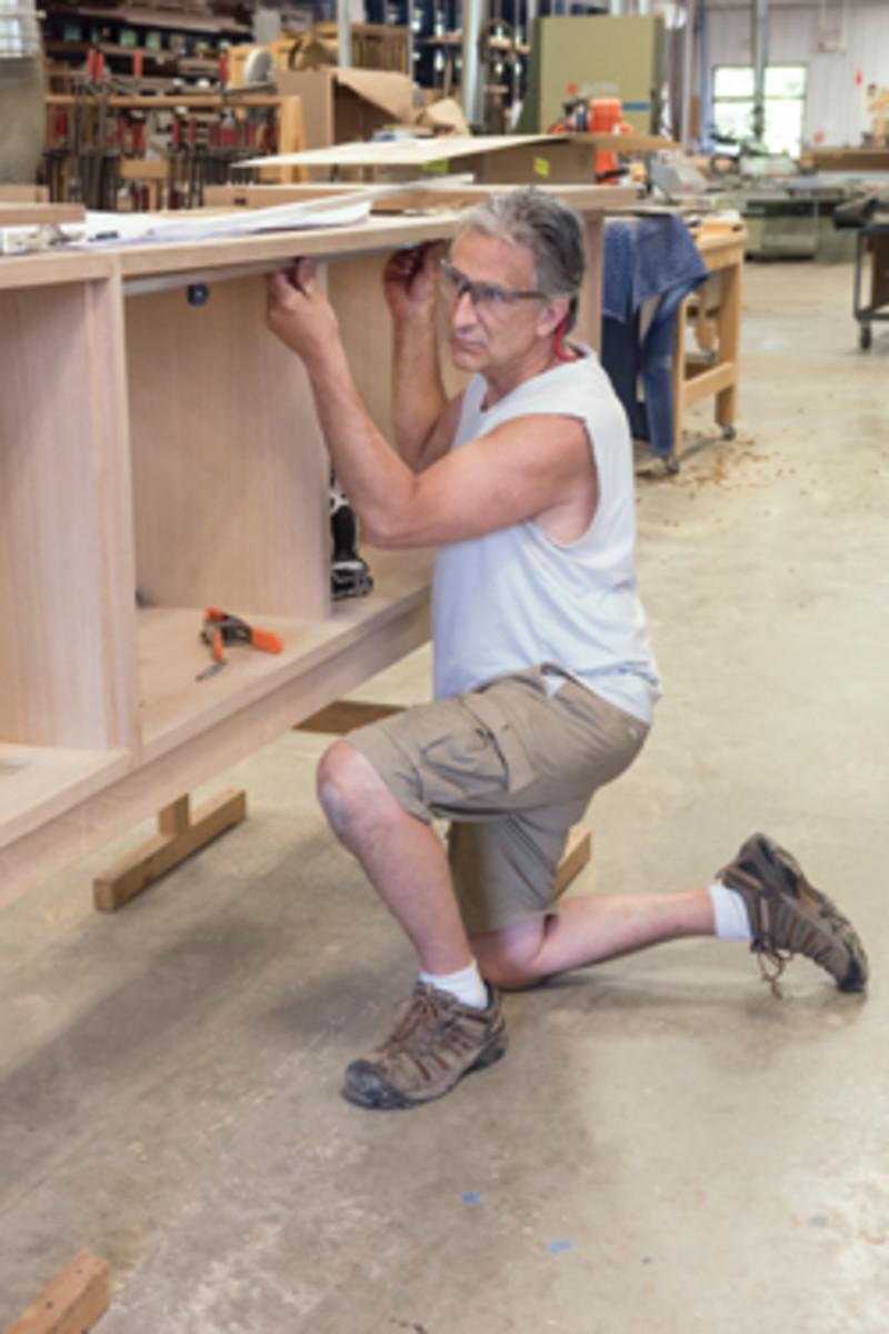 Bruton Strange installs drawer glides in a cabinet.