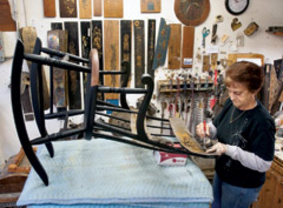 Employee Lorraine Lacasse sprays paint stencils.