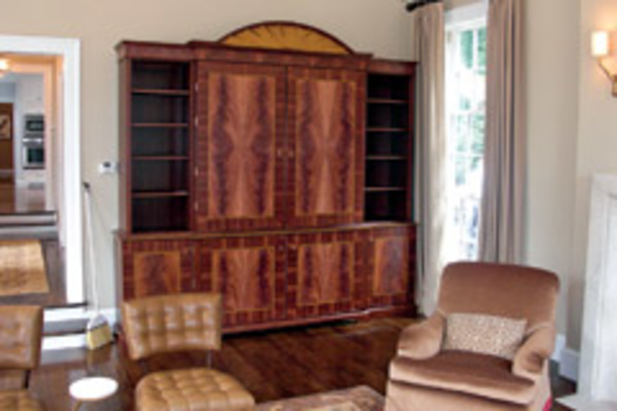 A mahogany wall unit with bookmatched crotch mahogany, satinwood inlays and pediment.