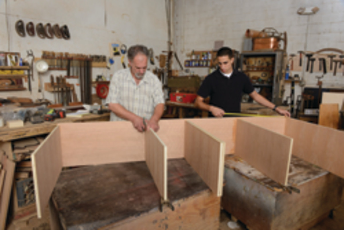 Head craftsman Scott Mulcahey, left, works on a cabinet commission with Marques.