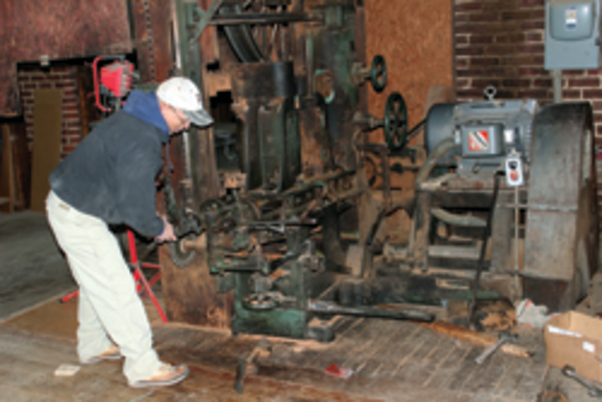 Employee Tony Rickard repairs the shop's 1920s McDonough reciprocating resaw.