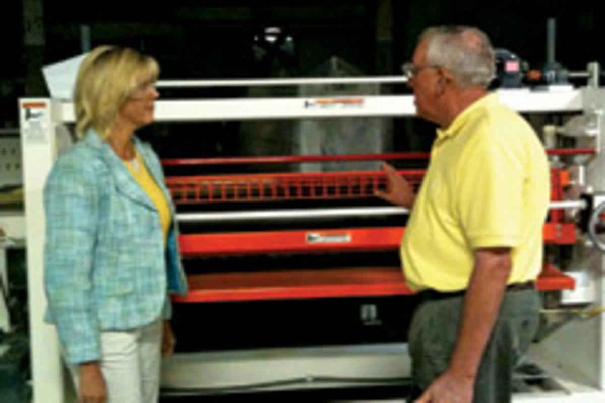 Skip Stachlewitz, COO of Black Bros. Co. in Mendota, Ill., discusses the features of the company's 775 adhesive spreader with Illinois state Sen. Sue Rezin as part of the WMMA's Patriot Award program.