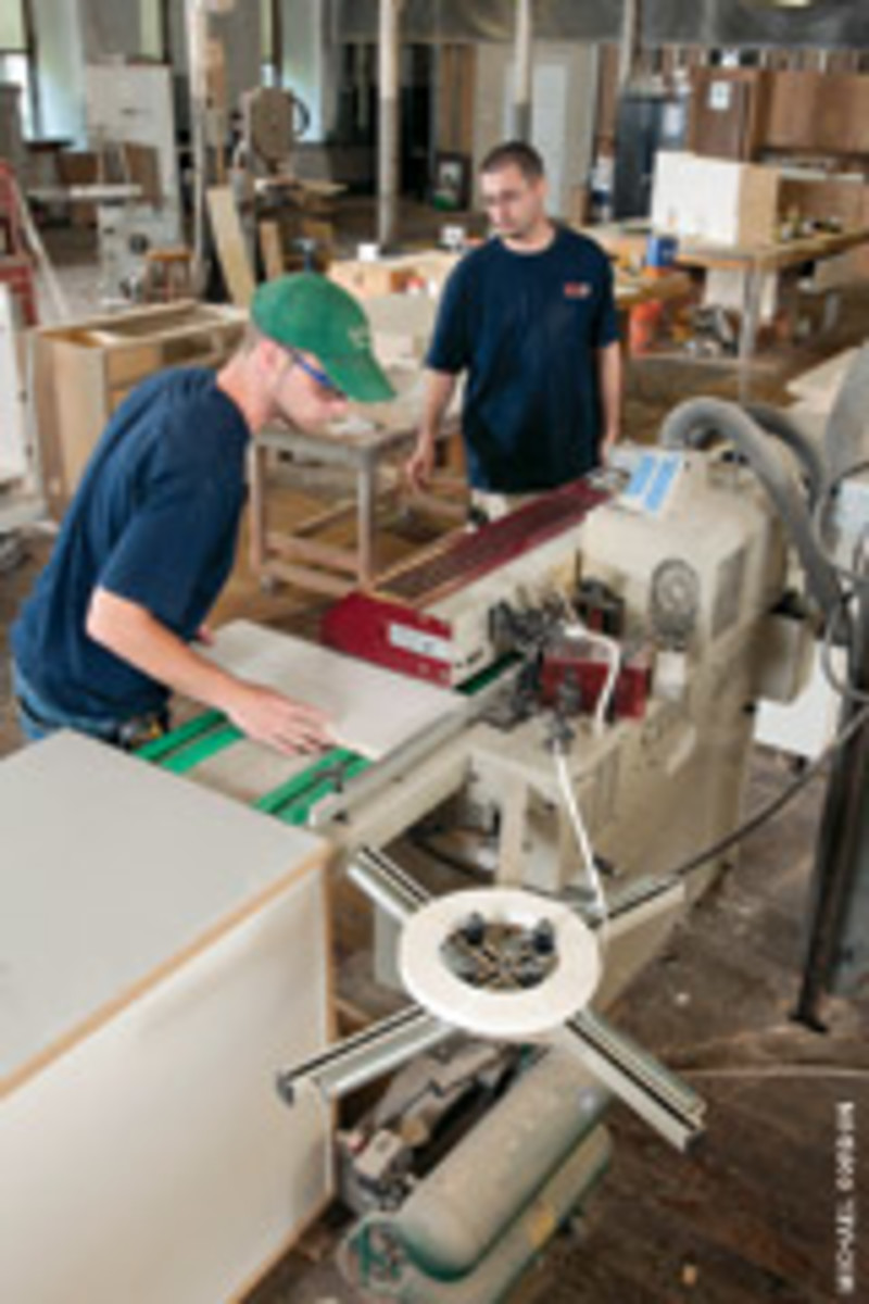 Employees Jareth Carlson, left, and Justin Sturdeuant operate the shop's edgebander.