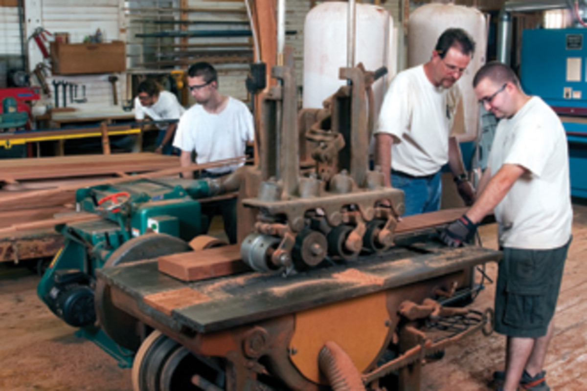 Randy Oullette, right, operates the shop's straight line rip saw.
