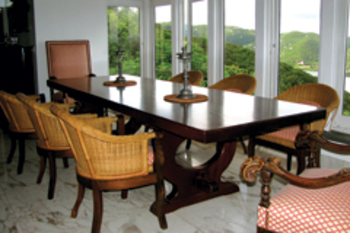 This solid mahogany trestle dining-room table sports a Mediterranean-inspired design by Scholz. It measure about 11 feet long by 40 feet wide and the top is more than 3 inches thick.