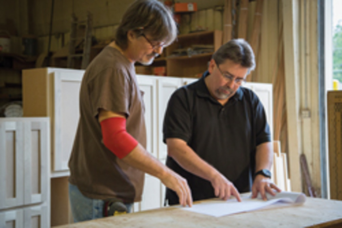Shop foreman Kevin Lettlefied and owner Dave Grounds review plans.