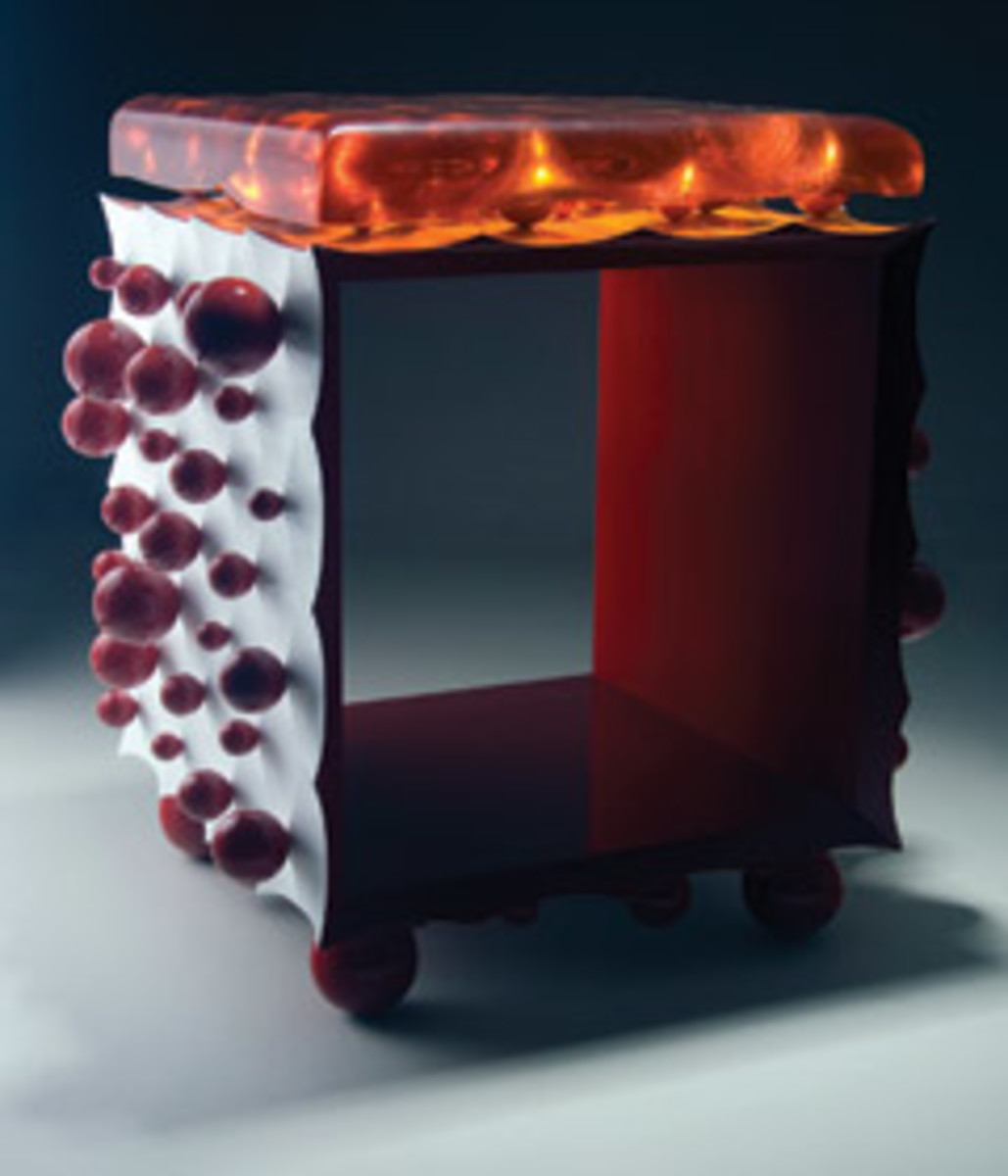 """""""Ball Side Table"""" is representative of Niswonger's new work. A low open table, the sides are painted white and carved into a pattern of points from which sprout shiny red bubbles. It has a removable top."""