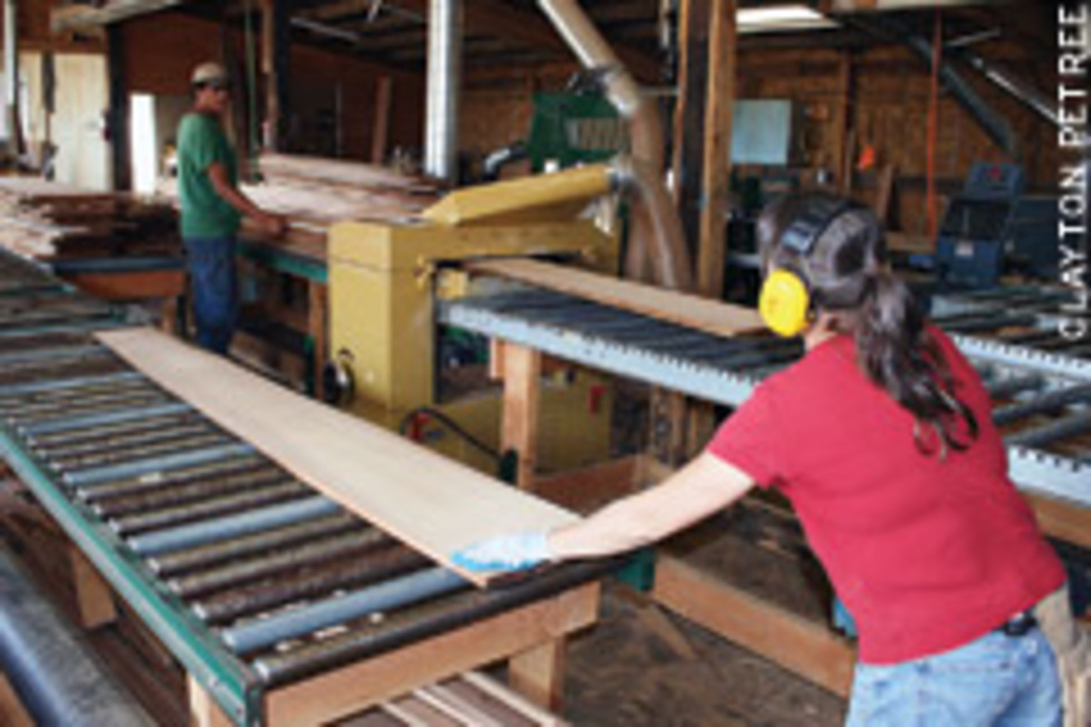 "Petree and Lauren Tracy process a run of live-edge fir in the Local Source Forest Products shop with a 25"" Powermatic planer."