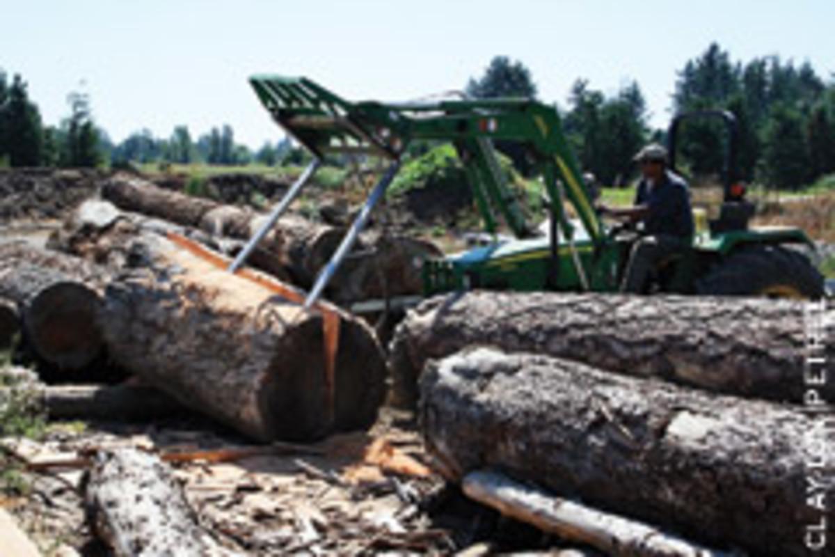 Petree splits a Douglas fir log with a John Deere tractor.