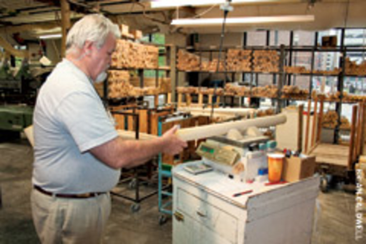 "Danny Luckett, CNC operator for the pro bat department at Hillerich & Bradsby Co., weighs a 3"" x 37"" ash billet to ensure it meets quality standards."