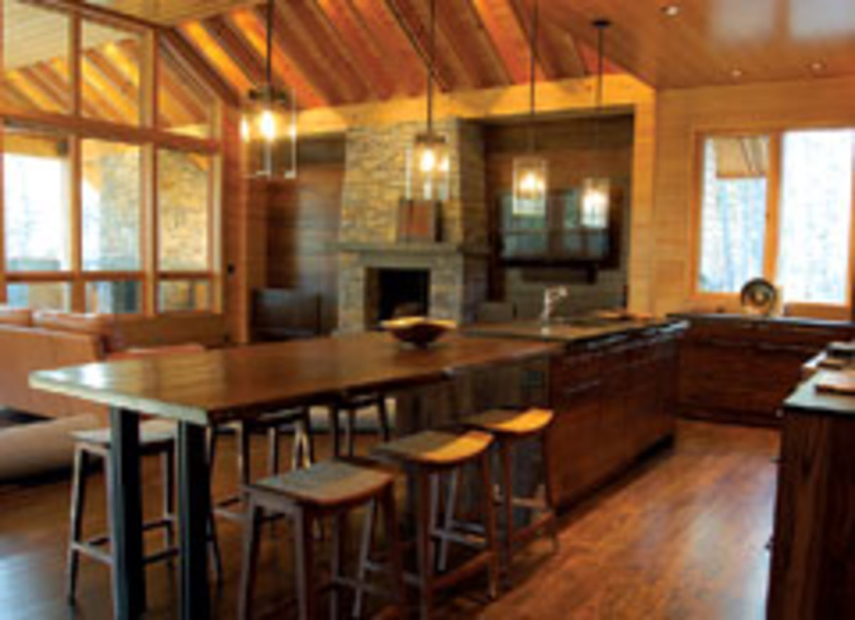 This kitchen features an island and dining table made with a reclaimed slab of walnut. The cabinets are made with wormy chestnut from a barn as well, illustrating the shop's preference to use recycled woods as often as possible.
