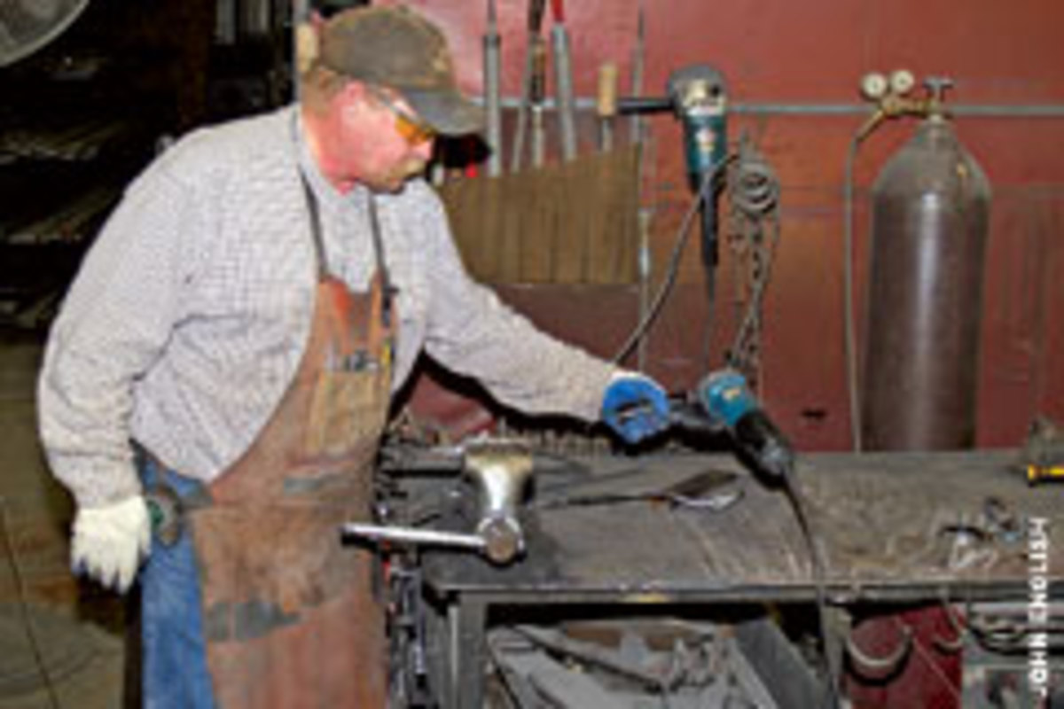 In-house blacksmith Joel Westberg reaches for a grinder to soften the edges of a custom-made hinge.