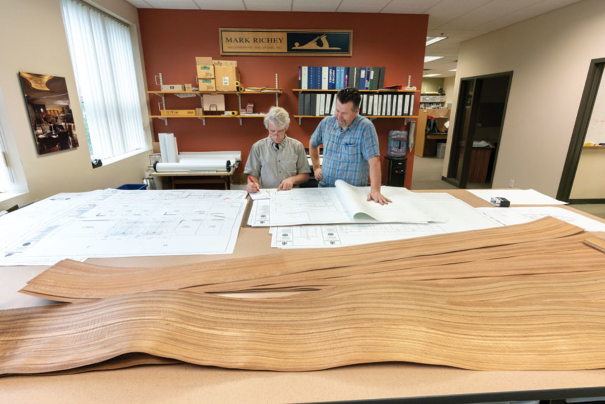 Project engineer Paul Buttrick, left, and Dave Jasneski, look at plans and veneer samples.