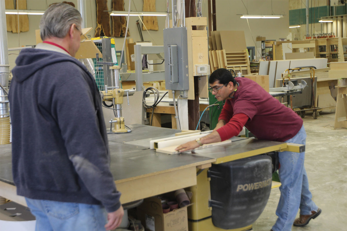 Shop foreman Chuck Buck observes Juan Alfano at the table saw.