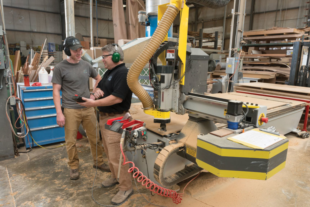 Sean Coyne, left, and shop manager Ned Karjanen talk next to the shop's MultiCam 3000 series CNC.