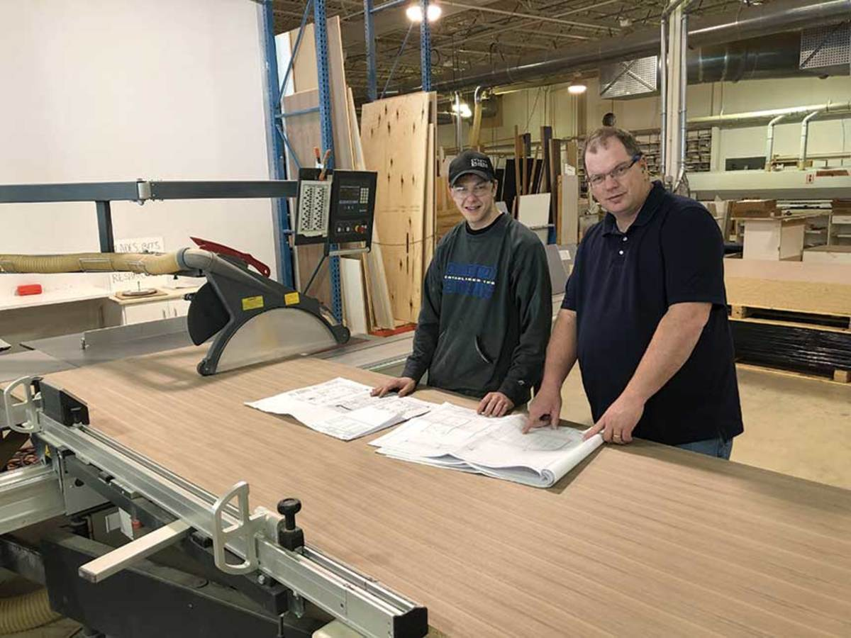 St. Paul grad Andrew Hilby (left) with Jeff Stanway, plant manager of O'Keefe Millwork.