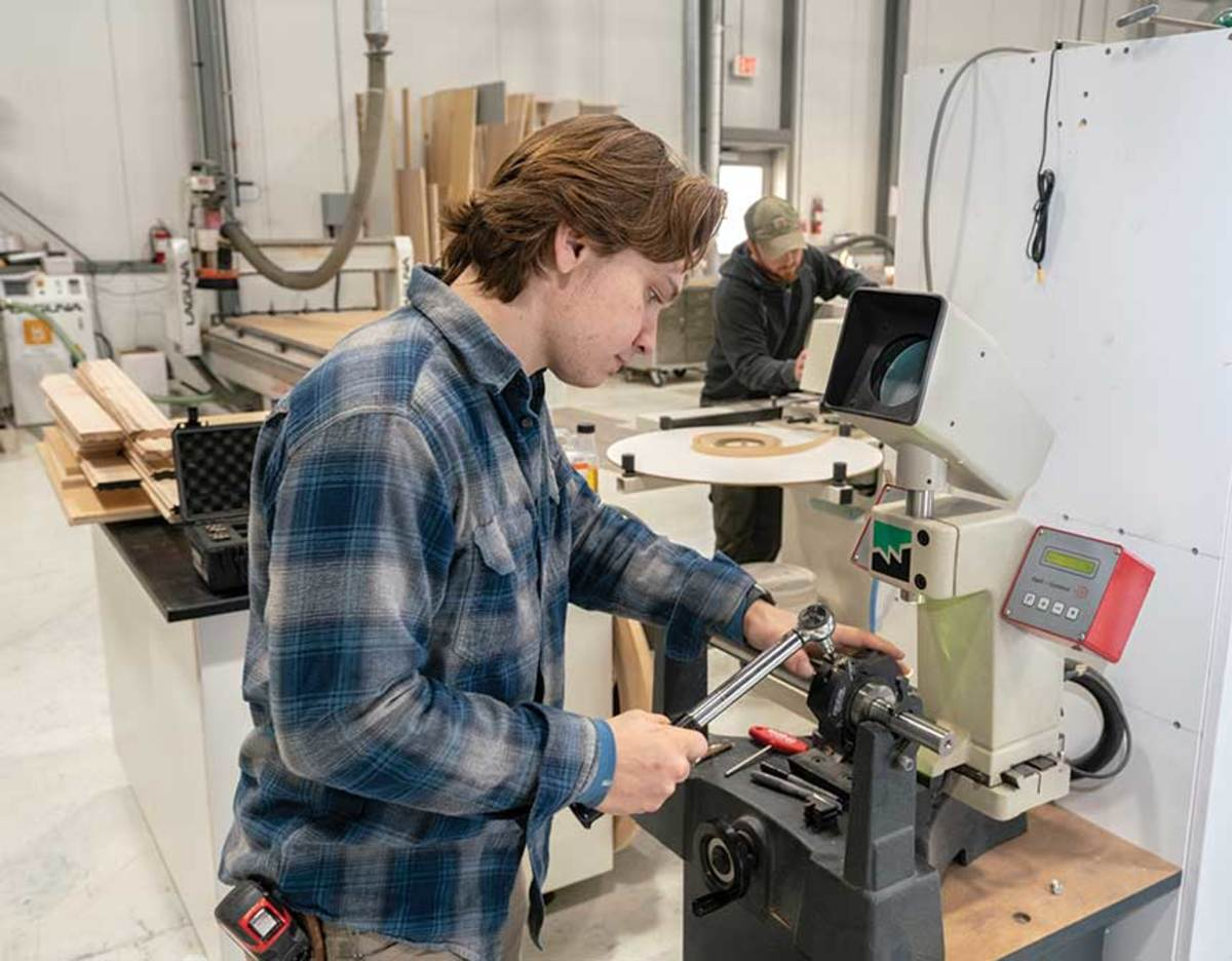 Tim Criscitello aligning the knives on a toolhead for its Weinig Unimat 218 molder/shaper.