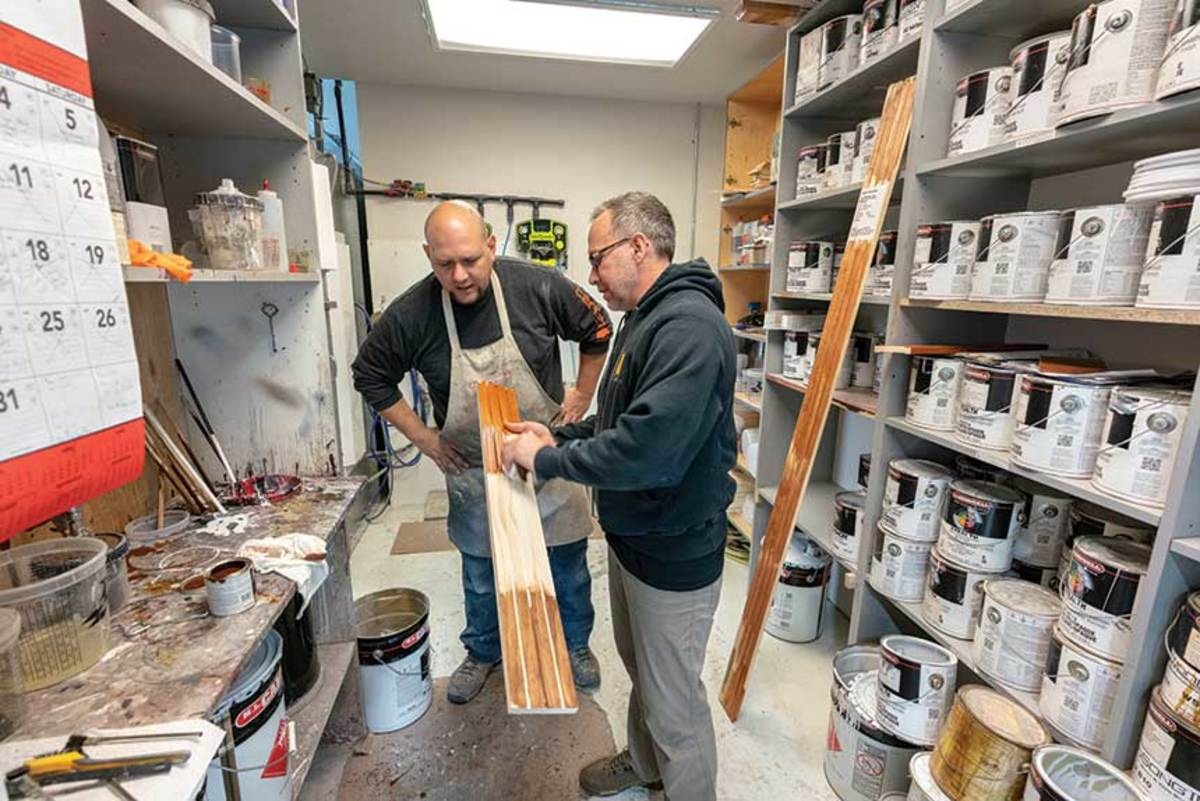 Eric Criscitello (right) and finisher Chris Weems consult on stain color matching.