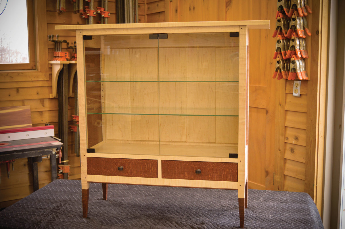 The Maple Display Cabinet from Thomas William Furniture with leopardwood, glass doors and shelves, and a clear lacquer finish.