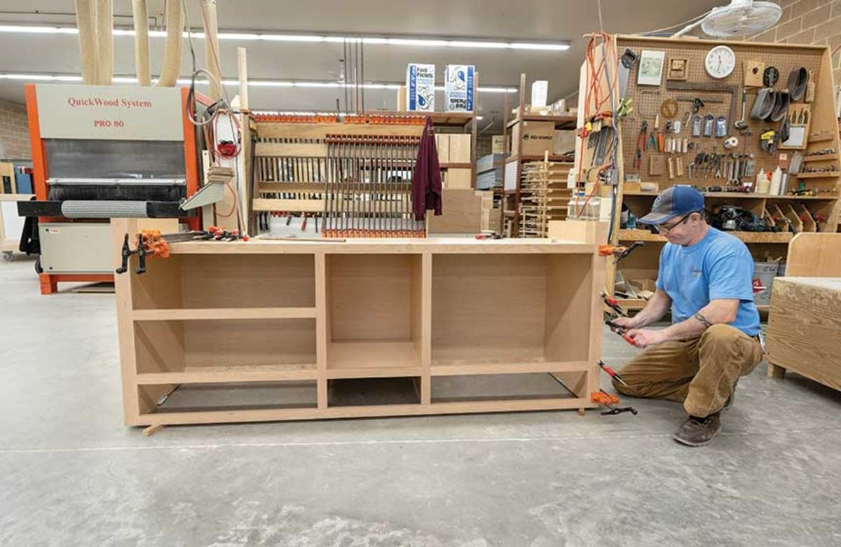 Employees Luke Hunter attaching the face frame to a cherry kitchen island.